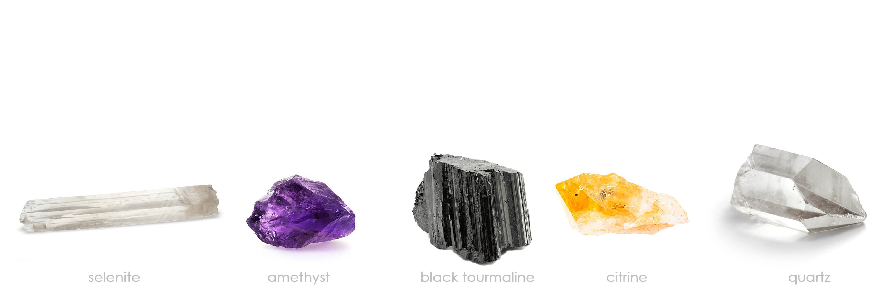 banner image of five crystals on a white background. Left to right: selenite, amethyst, black tourmaline, citrine and quartz.