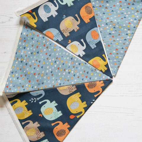 9 pennant string of bunting made from cotton fabric which is dark blue with elephants in different colours matched with a light blue patterned cotton fabric
