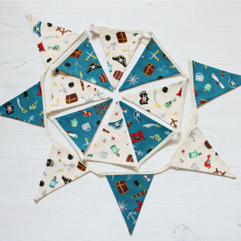 Pirate mini cotton bunting; 7 ivory pirate pennants with 7 blue pirate pennants all have pirate items on eg treasure chests, flags, swords etc