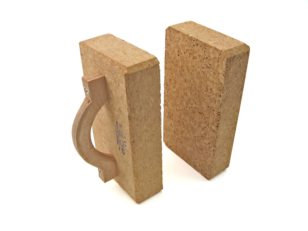 Dense rectangular corks with wooden handles for hot glass working.