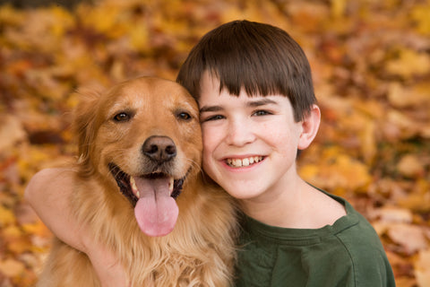 dog with kid in fall leaves