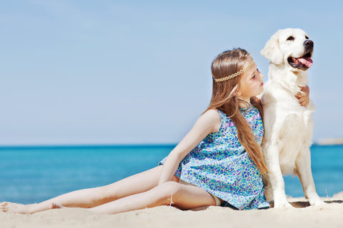 Girl sitting on beach with her pet labrador