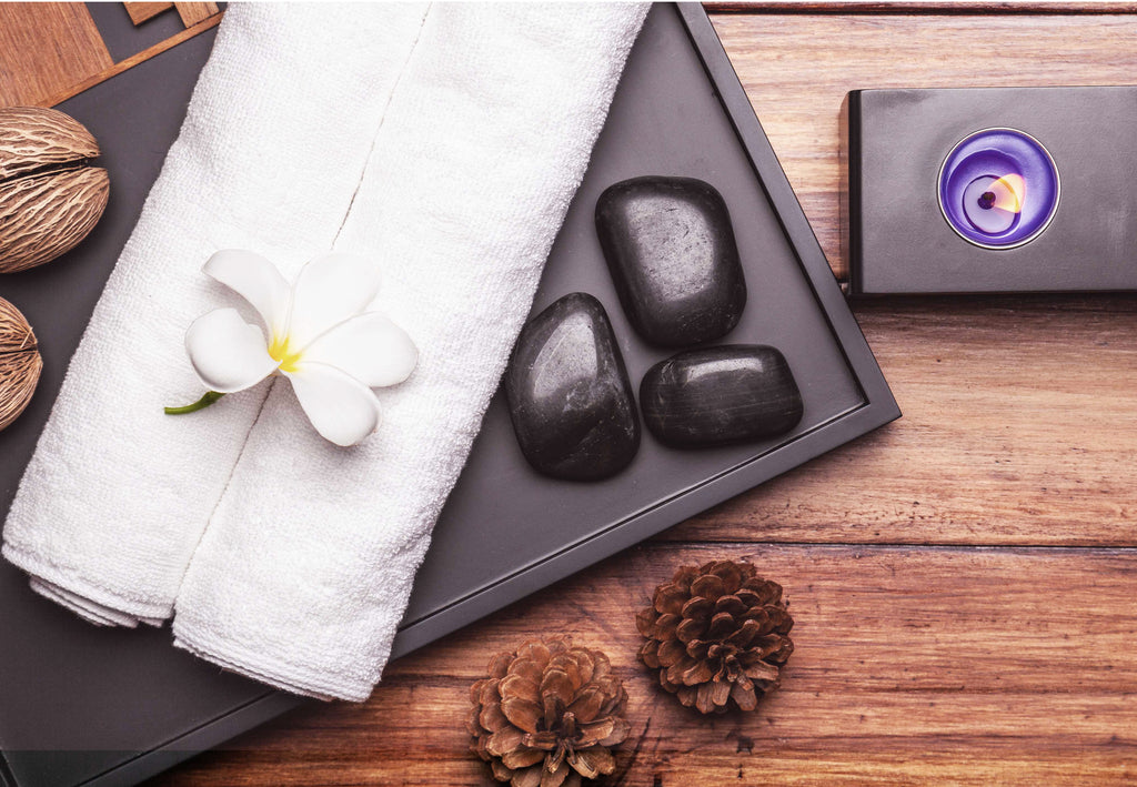 Korean Spa essentials with hot stones, a flower, and a candle.