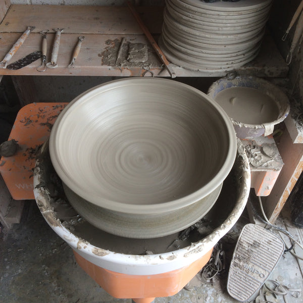 Making plates on the potter's wheel