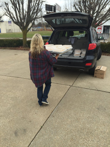 Kim carrying frozen casseroles to her vehicle to be whisked off the the kitchen.