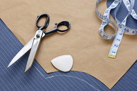 Scissors, fabric, and a measuring tape, laid out after having just cut out a custom pattern.