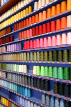 A wall whose shelves are quite full of spools of thread. There are many different colors of thread on the spools.