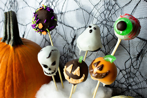 Spooky Cake Pops in the shape of an eyeball, pumpkins, a ghost, a skull, and decorated with sprinkles