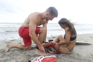 Ocean Rescue By Lifeguard Applying Tourniquet to Injured Surfer