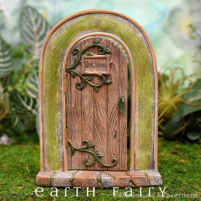 polyresin opening fairy door, featuring an arch with swinging, opening door, with a plaque with the word believe enscribed upon it