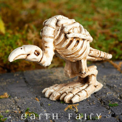 Miniature Buzzard Skeleton Figurine, shown in a garden setting,  from The Fairy Garden Miniature Halloween Collection by Earth Fairy