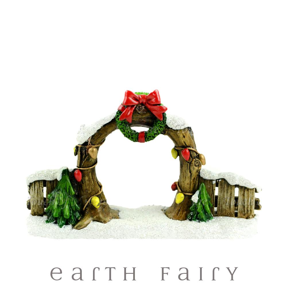 miniature fairy garden archway, christmas themed with snow and christmas wreath and christmas lights