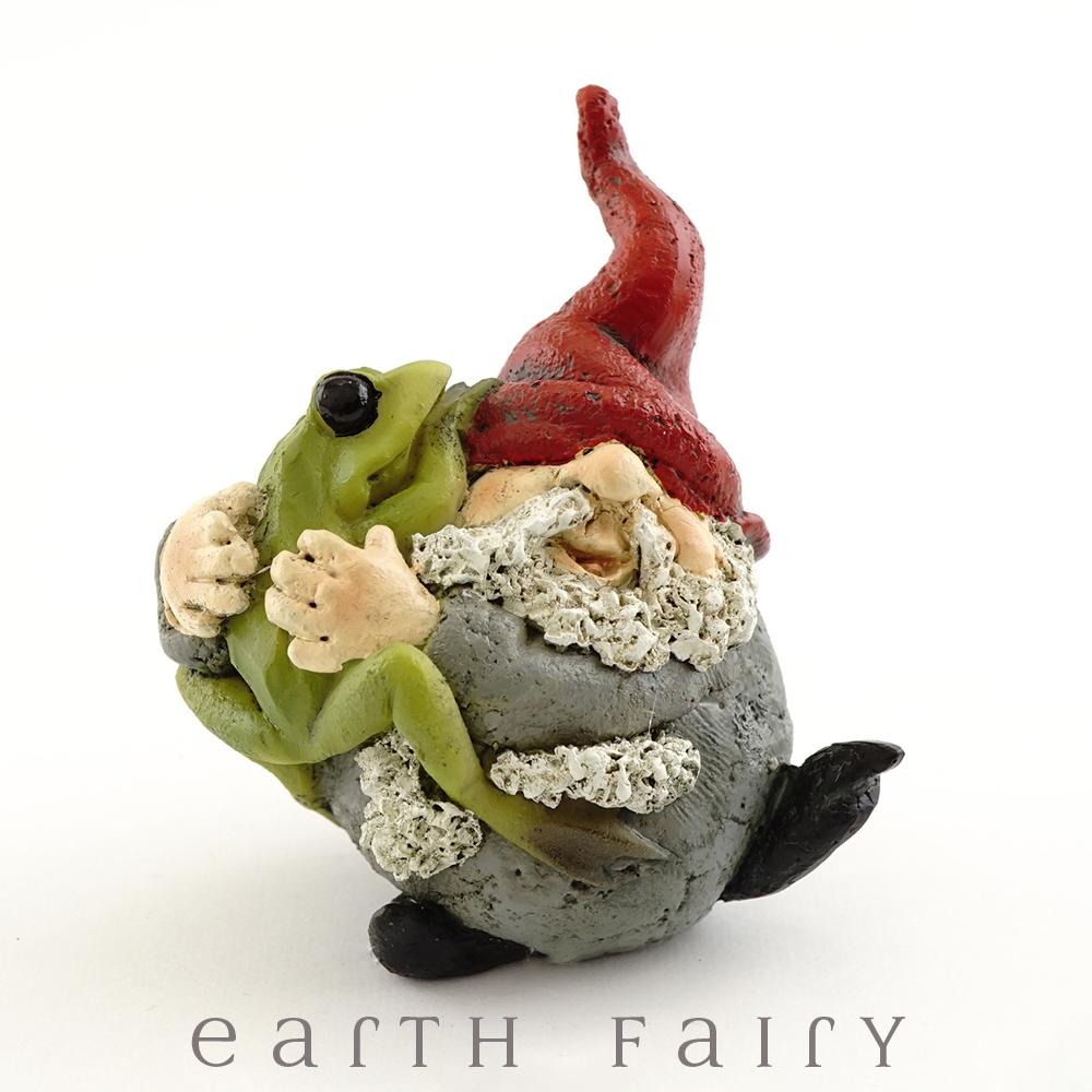 Miniature Polyresin Gnome Figurine - depicted standing in a grey suit and red pointy hat, giving a big hug to a large green garden frog