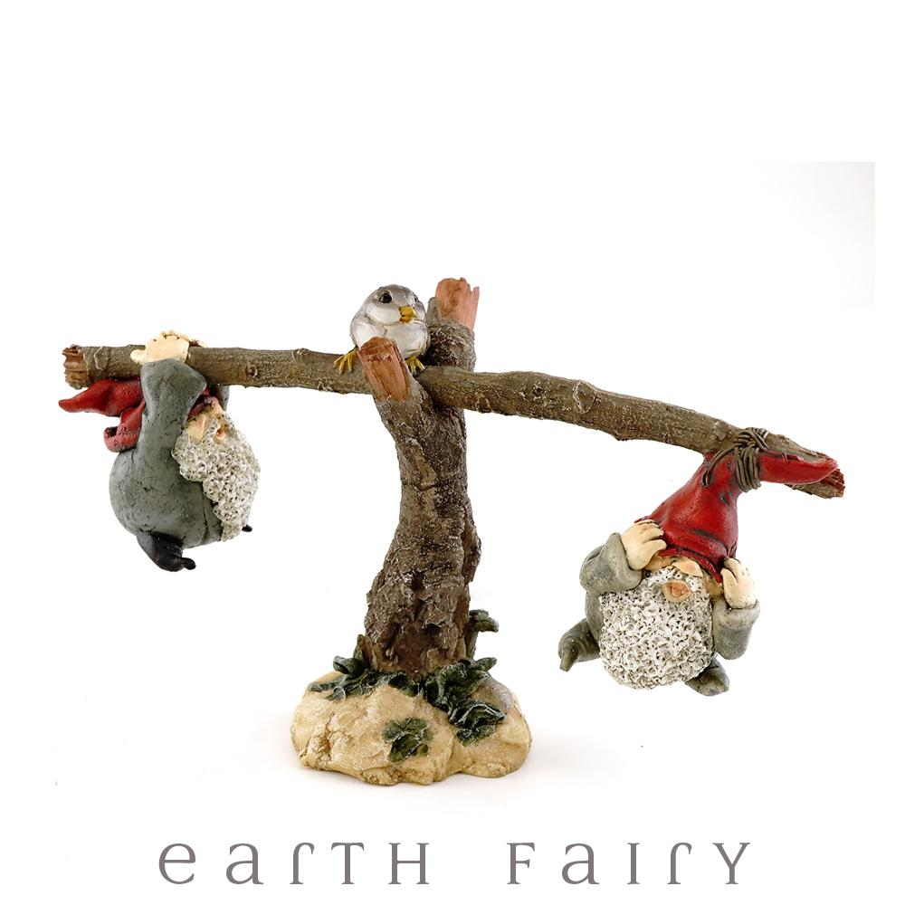 Miniature polyresin gnome figurines, depicting two gnomes playing on a seesaw, with a little bird on top of the seesaw's tree base