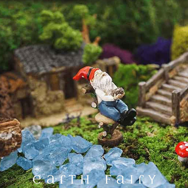 miniature polyresin gnome figurine, posed laying back on a log hewn chair, black boots, blue overalls, red pointy hat and clasping a nest full of eggs