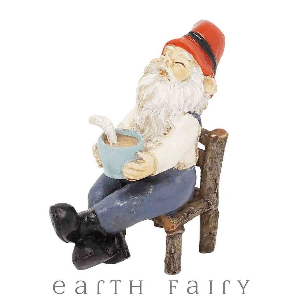 miniature polyresin gnome figurine, posed sitting on a log hewn chair, black boots, blue pants, cream top and red pointy hat, holding a mug of coffee