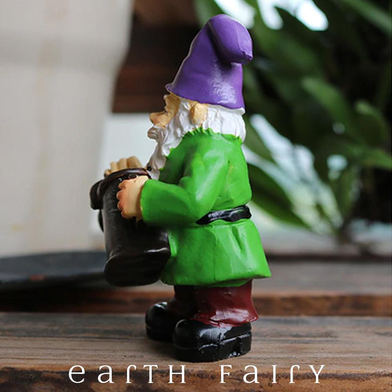 Gnome with Watering Can, brown boots and Green Coat with a Purple Hat and a White Beard holding a rusty watering can in his arms