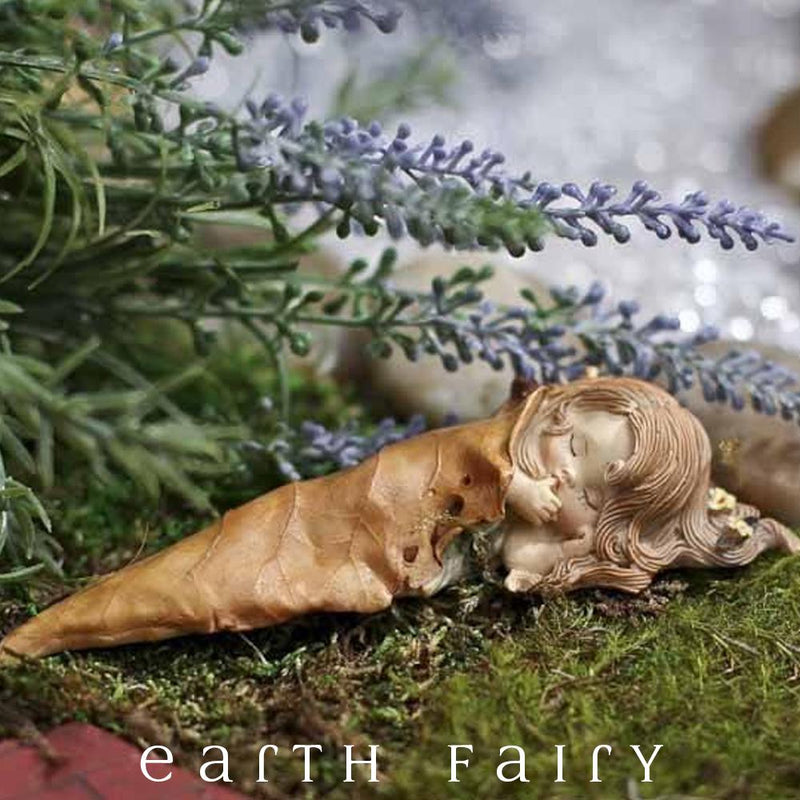 Little Fairy Sleeping Under a Golden Leaf Used as a Blanket, Eyes Closed, Hand at Mouth