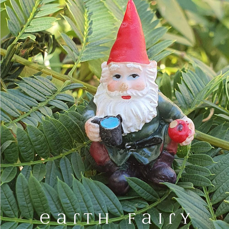 miniature polyresin gnome figurine, wearing boots, red pants, green coat and red pointy hat, posed sitting with a drink and holding an apple
