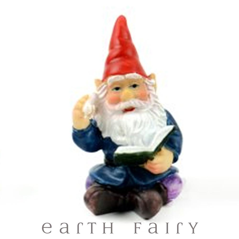 Miniature polyresin gnome figurine, dressed in boots, purple pants, blue coat and red pointy hat, sitting with a book