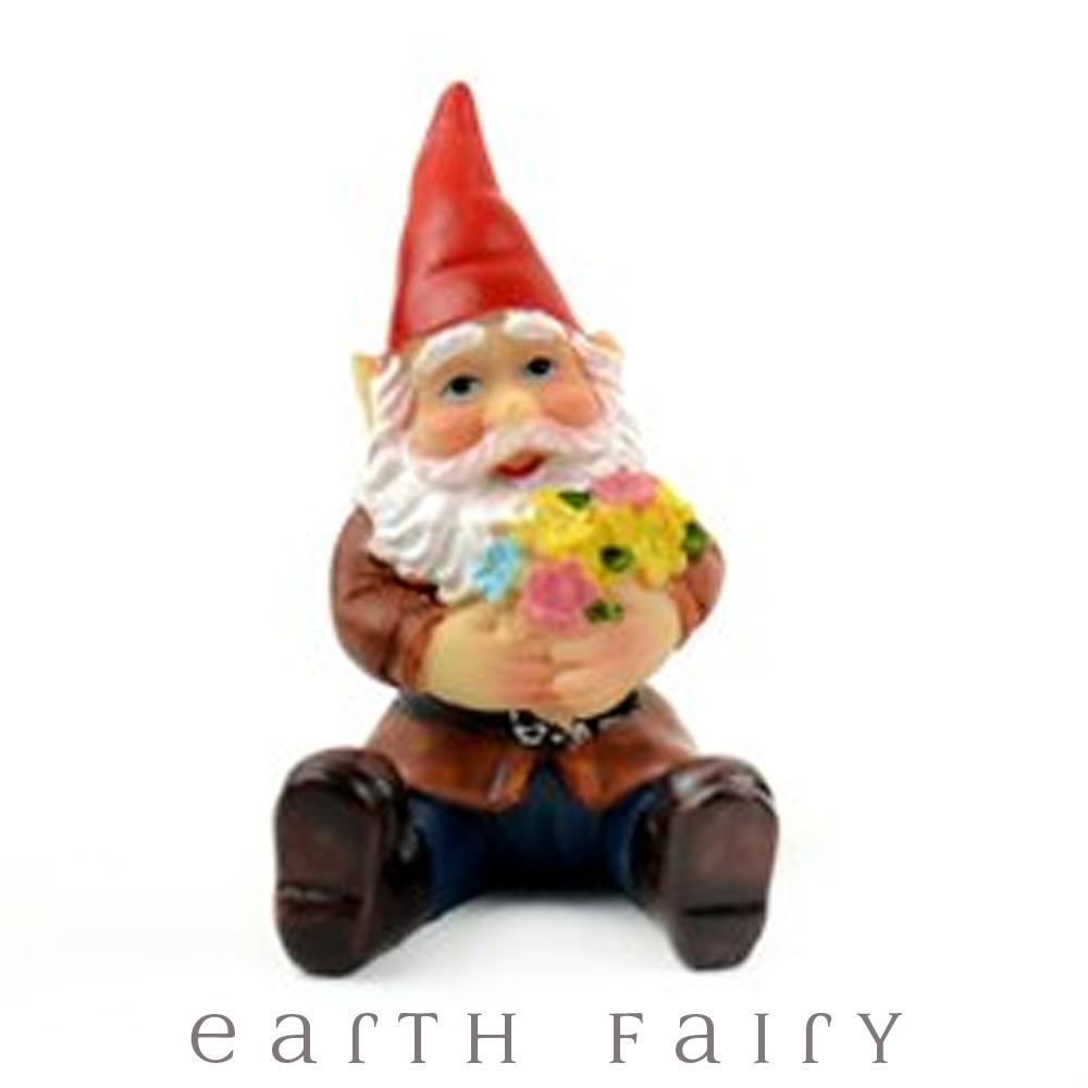miniature polyresin gnome figurine, wearing boots, blue pants, orange coat and red pointy hat, posed sitting and clasping a bunch of bright flowers