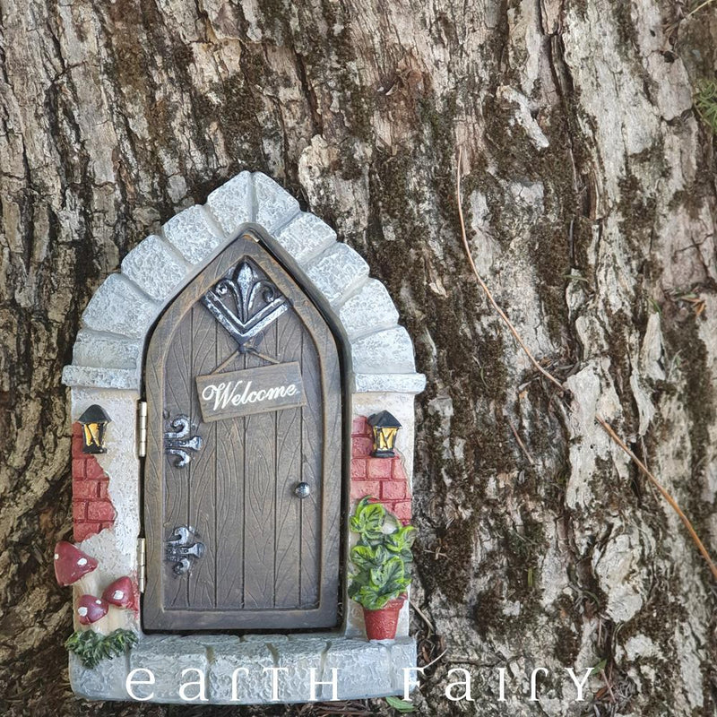 "polyresin miniature fairy door, arched cobblestone frame, with wood effect door and hanging ""welcome"" plaque, toadstools to one side, pot plant on the other side"
