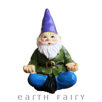 Yoga Gnome, wears blue pants and green belted coat with a purple hat and sits in a classic yoga pose