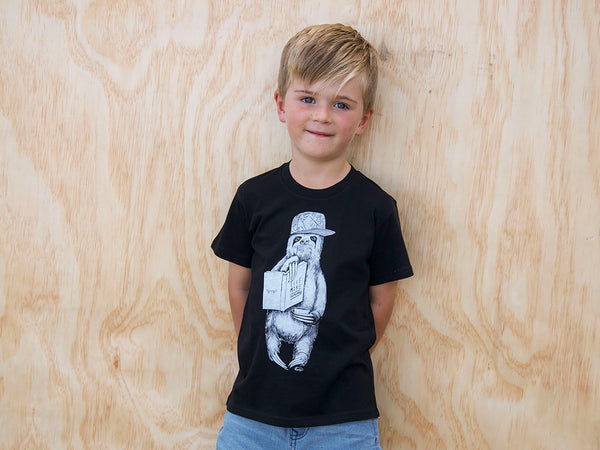 Boy modelling The Paper Rain Project's fair trade, organic kid's sloth tee. Design by Monique Richards in support of the Live More Awesome charity.