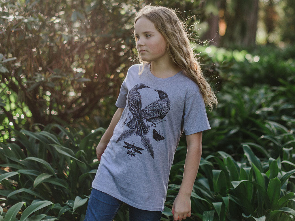 Girl modelling The Paper Rain Project's fair trade, organic kid's grey Two Tui t-shirt. Designed by Flox and supporting Conservation Kids NZ.