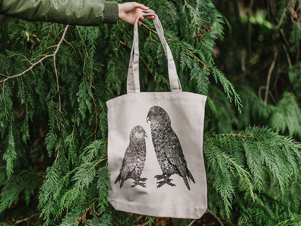 Kea hemp tote bag held in front of greenery, designed by guest artist Toby Brunsdon for The Paper Rain Project in support of The Wildlife Hospital, Dunedin.