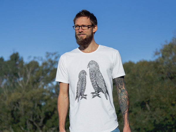 Man modelling The paper Rain Project's fair trade, organic white kea t-shirt, designed by Toby Brunsdon and in support of The Wildlife Hospital, Dunedin.