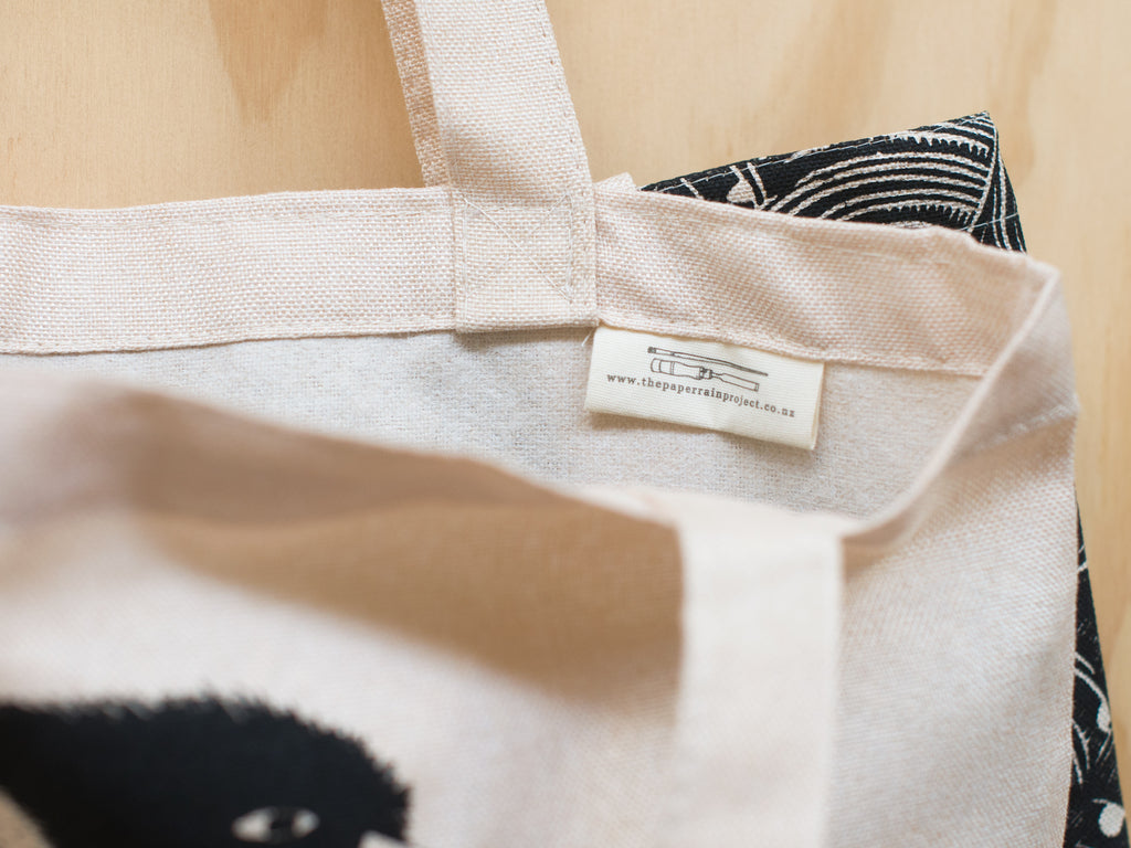 Close up of The Paper Rain Project tag on the kiwi hemp tote bag designed by Studio Soph' and in support of Conservation Kids New Zealand.