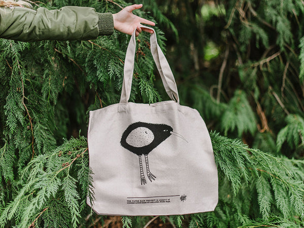 Kiwi hemp tote bag held in front of greenery, designed by Studio Soph' for The Paper Rain Project and in support of Conservation Kids New Zealand.