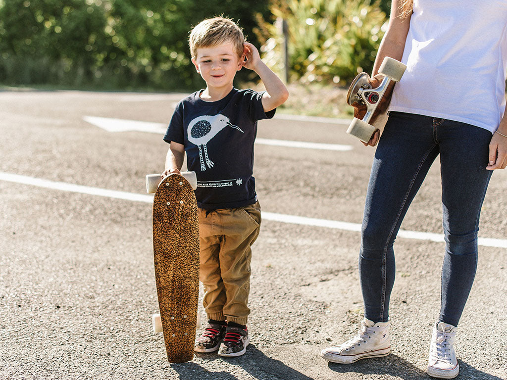 Young child with a handcrafted blackwood skateboard modelling The Paper Rain Project's fair trade and organic navy kid's Kiwi tee, designed by artist Studio Soph.