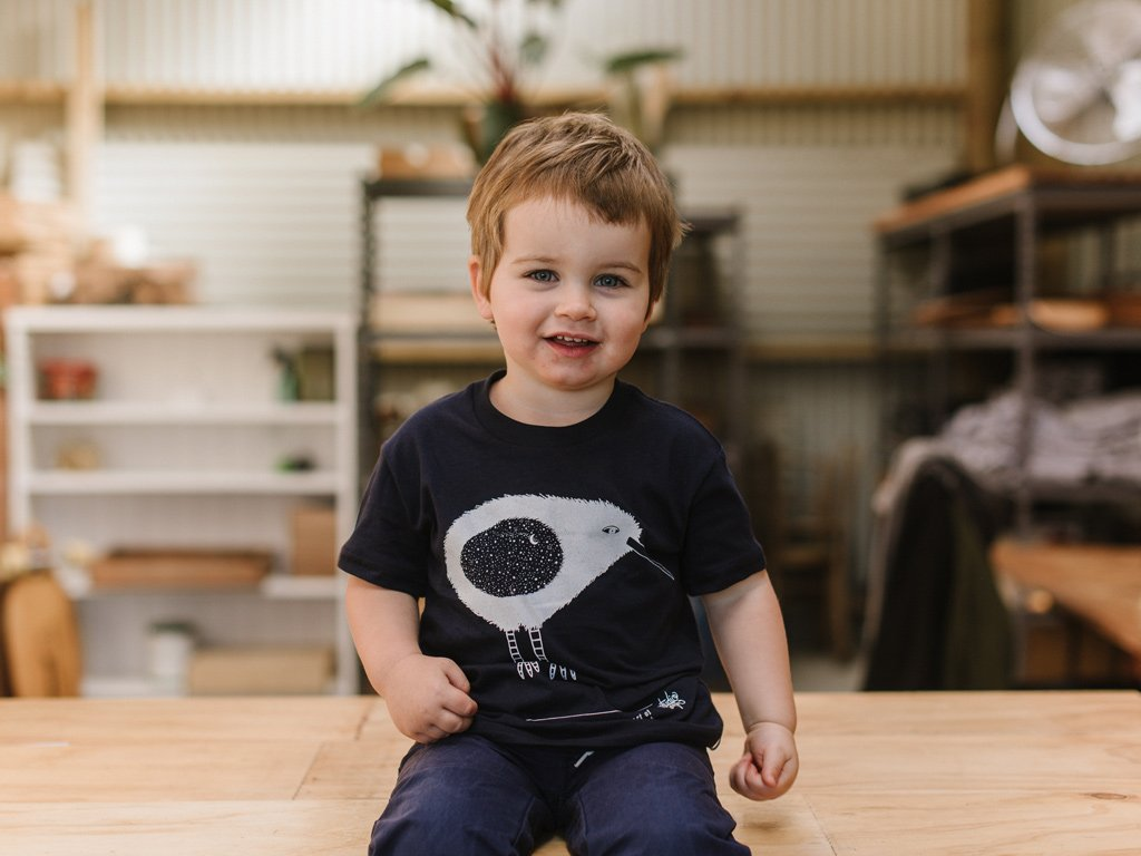 Toddler modelling The Paper Rain Project's fair trade and organic navy kid's Kiwi tee, designed by artist Studio Soph.