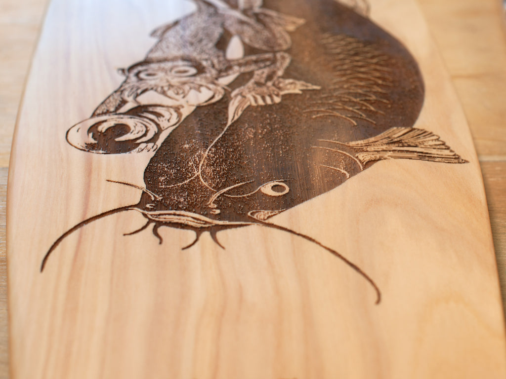 Close up of 'Namazu' designed by Morag Shaw laser etched onto sustainably sourced macrocarpa art board handcrafted by The Paper Rain Project.