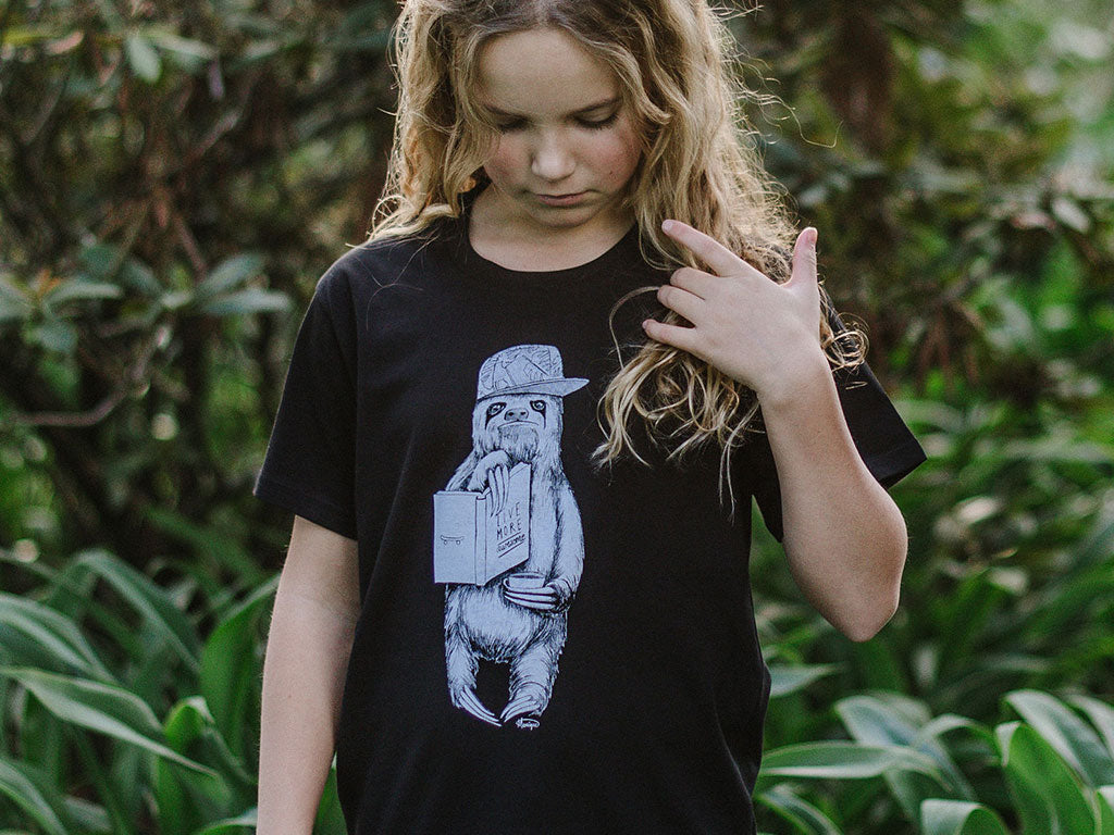 Girl modelling The Paper Rain Project's fair trade, organic kid's sloth tee. Design by Monique Richards in support of the Live More Awesome charity.