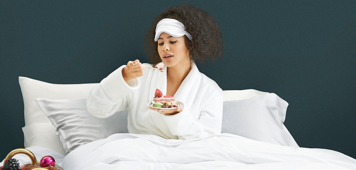 | Woman in bed eating dessert on silk pillowcases