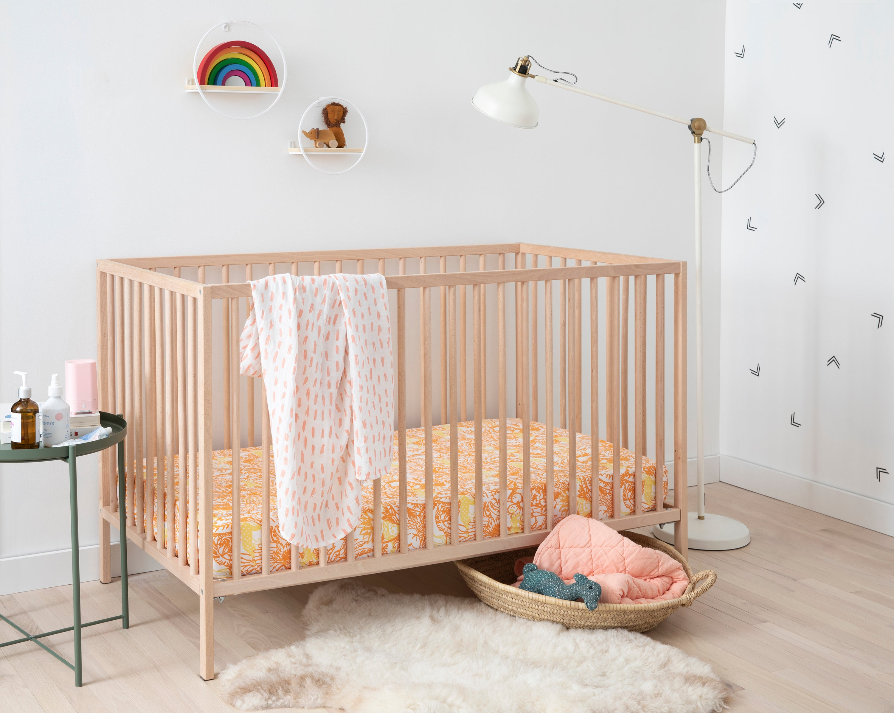 """Brooklinen's Crib Sheet Set in """"Jungle in Orange,"""" paired with the Baby Quilt and Swaddle in """"Blush."""""""