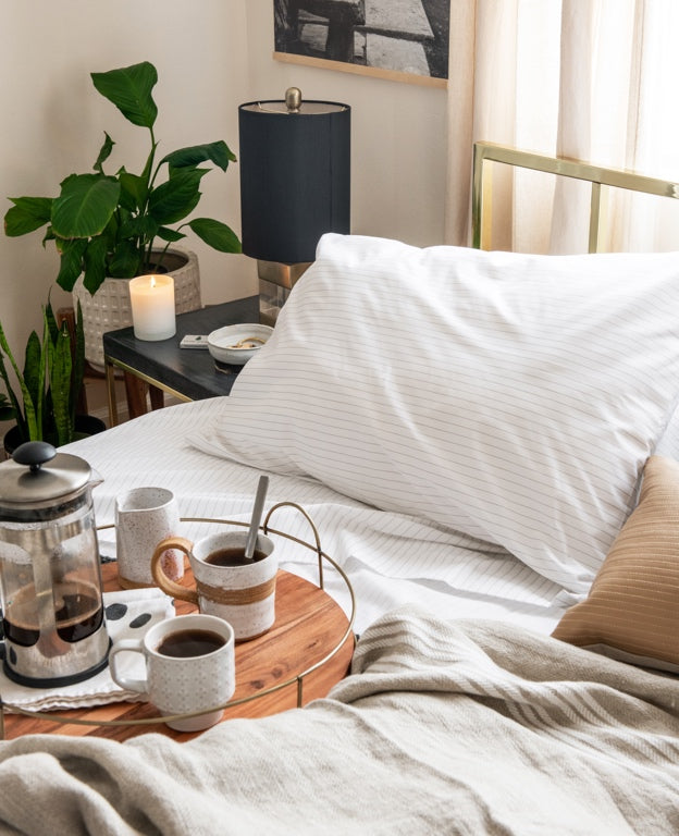 A French press sitting on a serving tray placed on a comfortable looking bed.