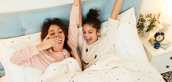 Lightweight Quilt and Pillowcases in Black Lorimer, fresh x Brooklinen Beauty Sleep Box | Two women yawning in bed promoting Brooklinen and fresh collaboration