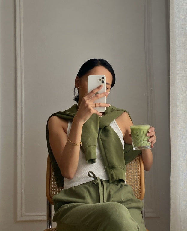 A sitting woman in green loungewear holding a candle.