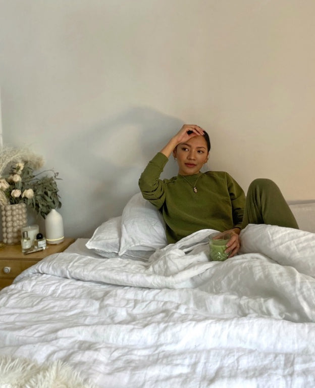 A woman reclines in a bed with white sheets while drinking tea.