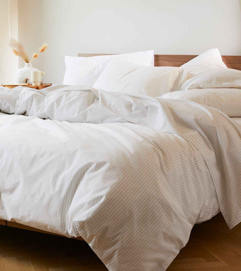 Big fluffy comforter on a bed with a light wood