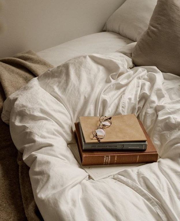 A stack of books rests on a warm looking white duvet.
