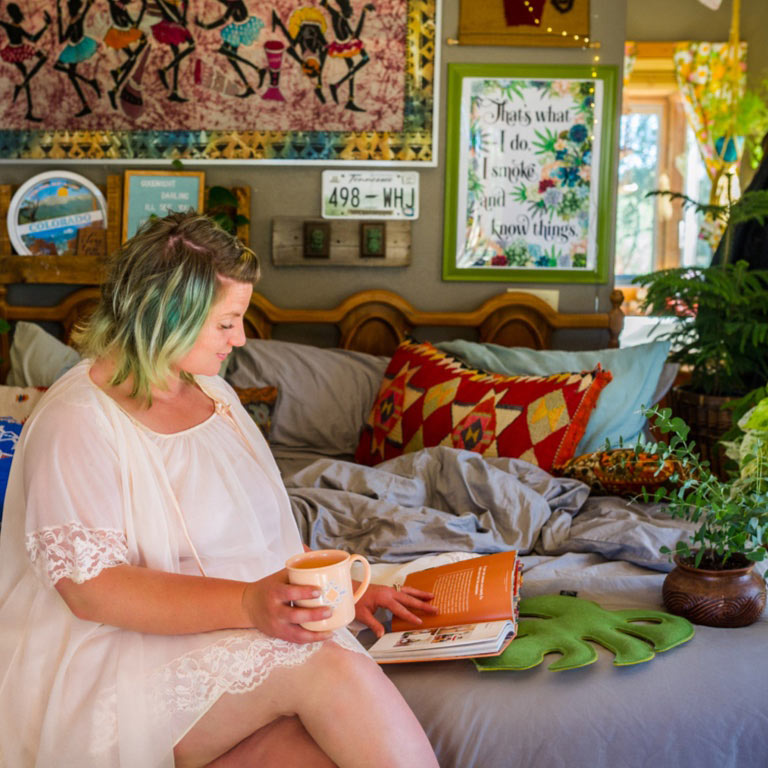 A woman sitting on a bed reading coffee