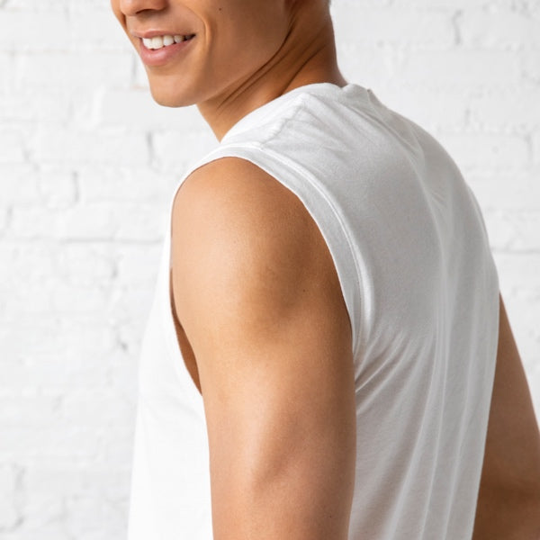 Man wearing a slim white tank smirks over his shoulder.