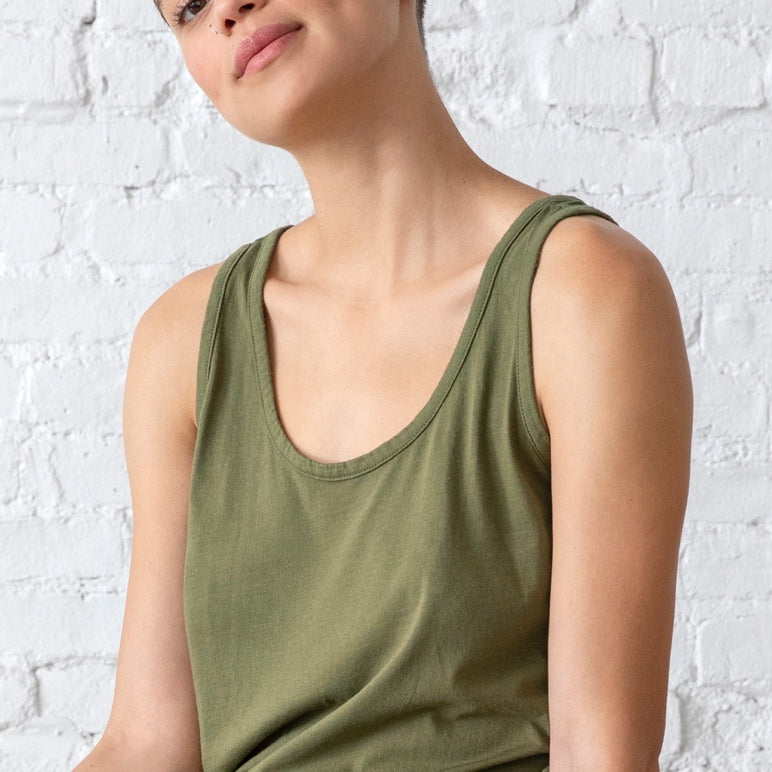 Woman casually poses with effortless style in a green tank top.