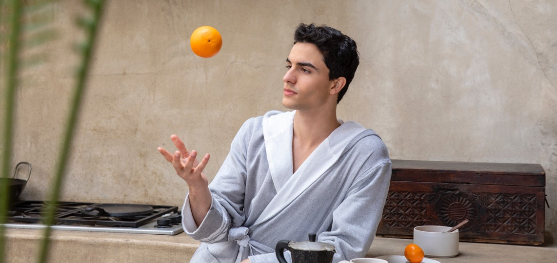 Man tosses an orange into the air while enjoying an easy day in a Hammam Robe.