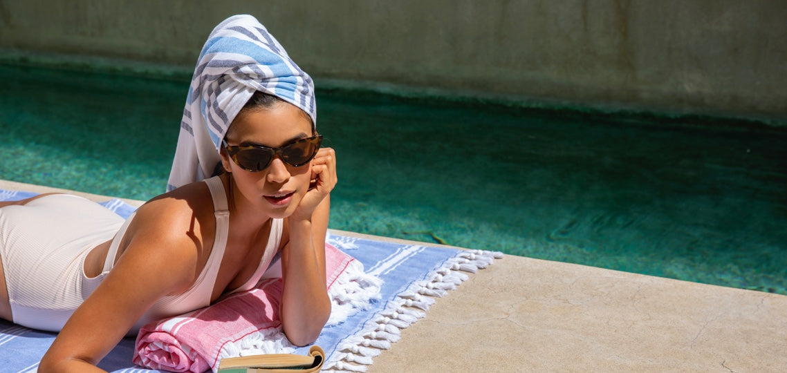 Woman in sunglasses lays out poolside on a Hammam Blanket, looking cool.